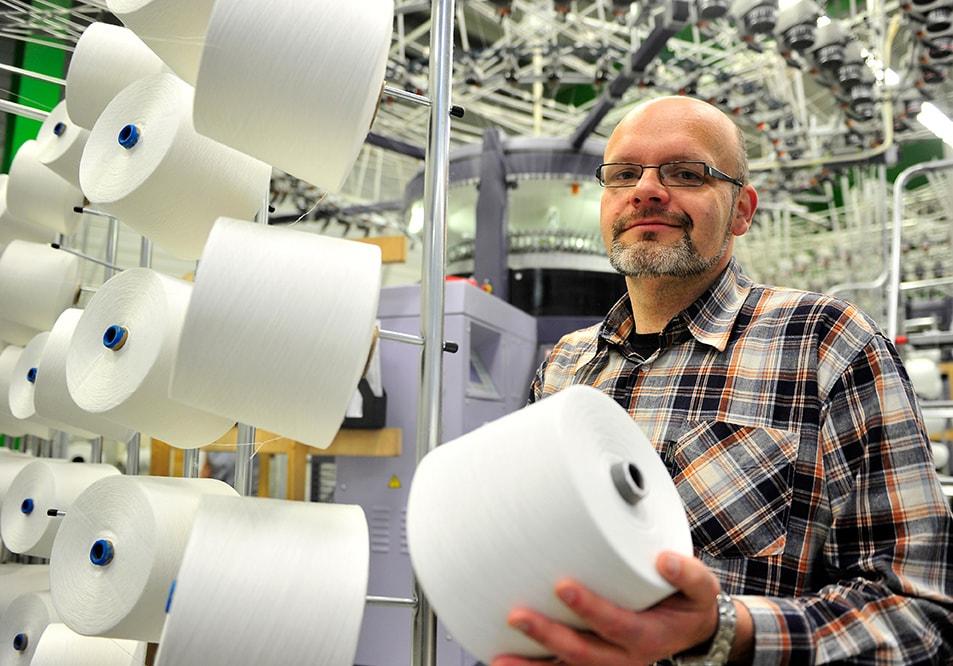 030410-0403/Grünbach-V./Das junge Textilunternehmen STS Textiles GmbH & Co. KG im vogtländischen Grünbach erweitert seine Produktionskapazitäten und will in diesem Jahr seine Belegschaft auf 25 Mitarbeiter aufstocken. Die Anfang 2008 gegründete Firma produziert gegenwärtig mit 17 Beschäftigten in rollender Woche Strickstoffe für Abnehmer in Deutschland, Österreich, der Schweiz, Polen und Tschechien. Bislang hat der aus Hof stammende Unternehmer in Grünbach rund 3,5 Mio. EUR investiert. Die hochmodernen Großrundstrickautomaten wurden in der Chemnitzer Terrot GmbH hergestellt.  Auf den Hightech-Anlagen entstehen vor allem strapazierfähige Matratzenbezugstoffe für die Heimtextilbranche. Rund zehn Prozent der Produktion gehen an andere Firmenkunden, die damit u. a. Autositze, Kindersitze oder Schutzhelme komplettieren. Bislang verließen rund 4 Millionen Laufmeter Maschenstoffe das Unternehmen. Unlängst hat sich STS erstmals auf der Möbelmesse in Stockholm präsentiert. Große Beachtung auf dem skandinavischen Markt fand die neue Produktreihe Sign of Nature®, eine ausschließlich aus Naturfasern wie Baumwolle und Leinen hergestellte Kollektion. Gegenwärtig ist in Grünbach ein ergänzendes Bio-Sortiment auf der Basis von Baumwolle aus kontrolliert biologischem Anbau (KBA) in Vorbereitung.  Im Foto:Unternehmer Markus  Tutsch
